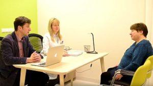 Врачи и пациент разговаривают о последствиях операции по удалению опухоли головного мозга